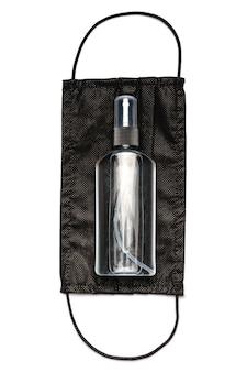 ローション、消毒剤または液体石鹸のボトルと明るい灰色の背景の上の医療用保護マスク。