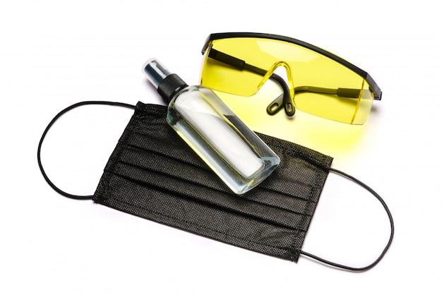 ローション、消毒剤または液体石鹸、保護ゴーグルグラス、クリッピングパスと白い壁に分離された防護マスクのボトル。