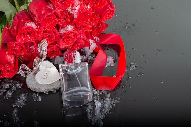 メンズ香水と木製のハートのボトル、ミラーリングされた背景にバラ