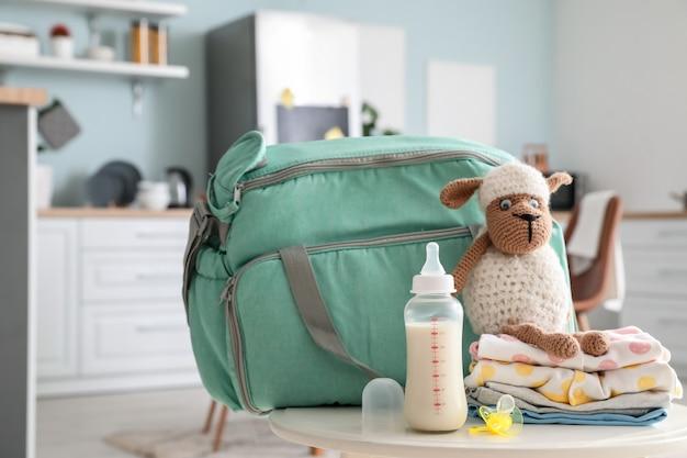 Бутылка молока для ребенка, сумка, одежда и игрушки на столе