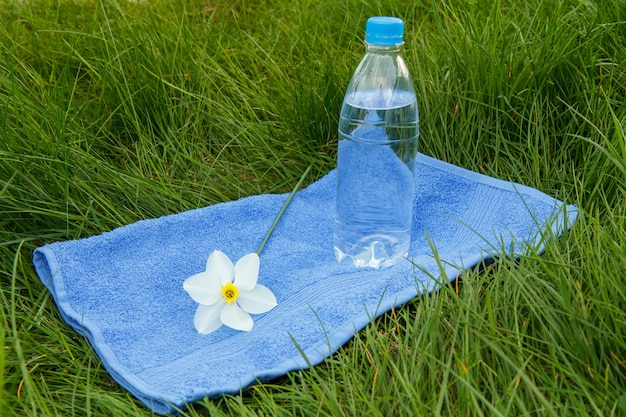 Бутылка минеральной воды, синее полотенце и бело-желтый нарцисс на зеленой траве