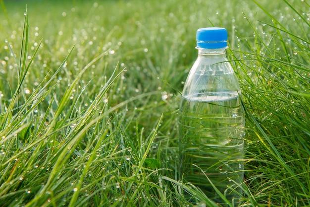 早朝に露の滴と緑の草の上のミネラルウォーターのボトル