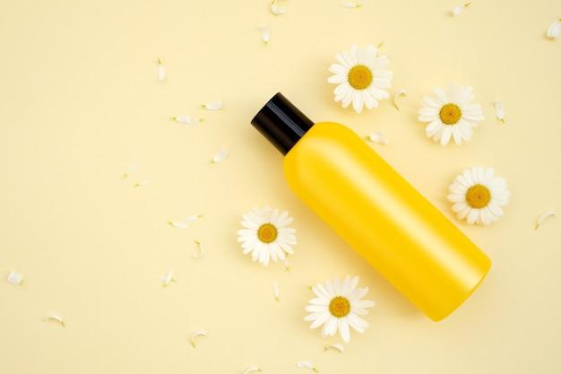Бутылка макета косметической продукции с цветами ромашки на желтом фоне