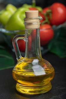 Бутылка оливкового масла перед свежими овощами.