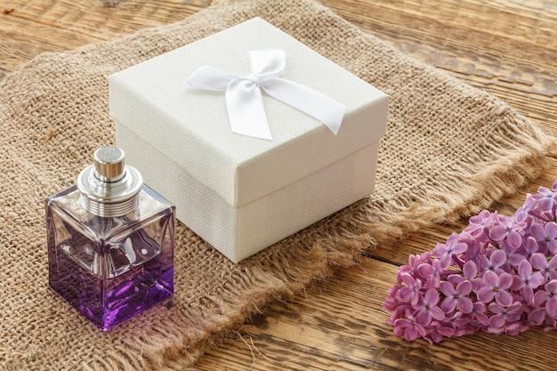 향수 한 병, 선물 상자, 자루천과 오래된 나무 판자에 라일락 꽃. 휴일에 선물을 주는 개념. 평면도.