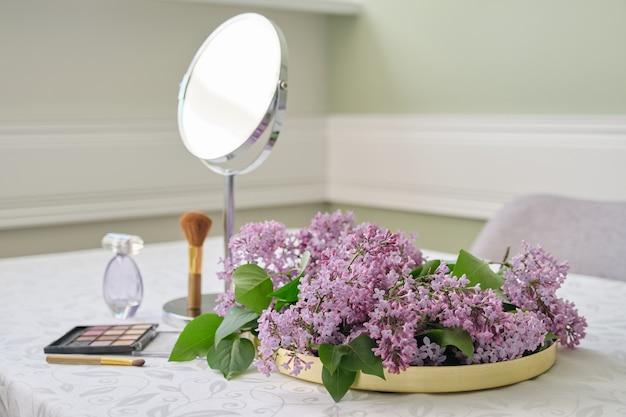 香水のボトル、ブラシ付きのアイシャドウ、テーブルミラー、新鮮なライラックの花