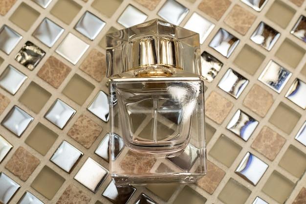 抽象的な金色の背景に香水のボトル。閉じる