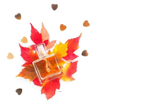 白、平らな横たわった赤黄色の紅葉の香水のボトル