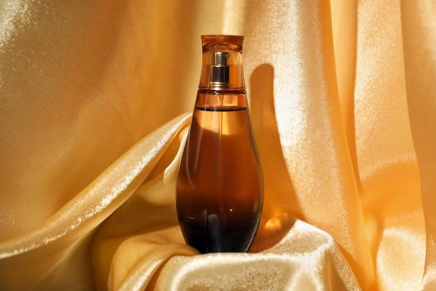 光沢のある生地に香水のボトル