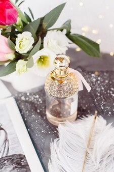 Флакон духов. весенний букет на сером бетонном столе. розы, тюльпаны и лизиантус. белое перо.