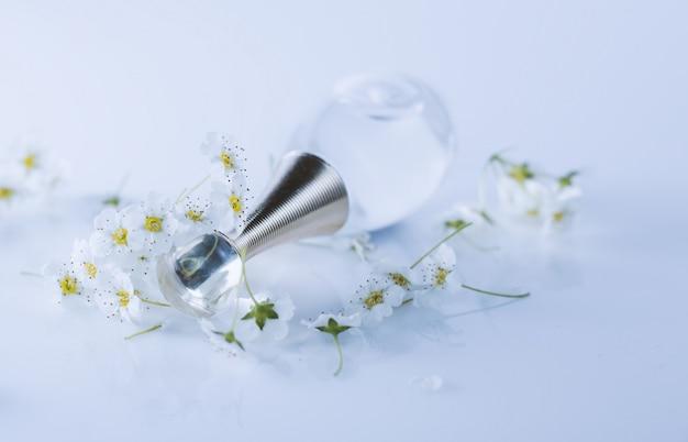 Флакон духов с ароматом цветов на белом фоне