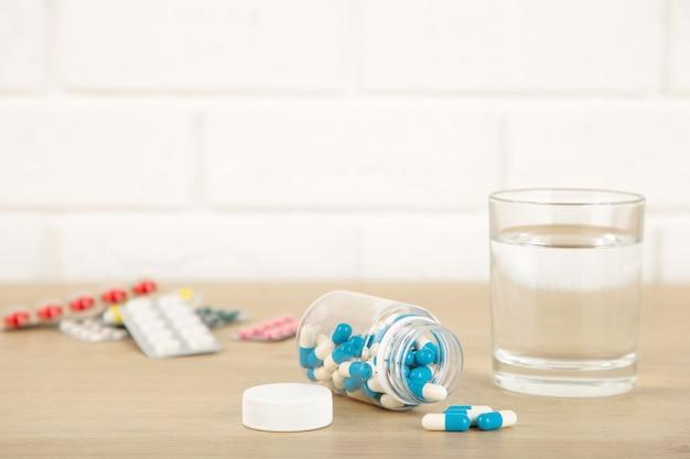 Бутылка таблеток и стакан воды