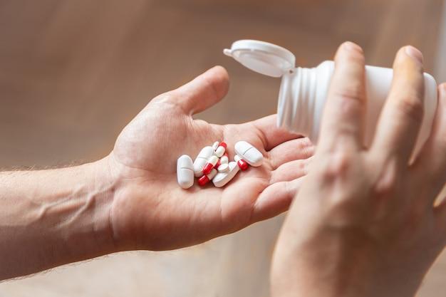 Бутылка таблеток, бросая различные лекарства в ладони