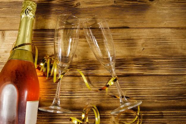 Бутылка розового игристого вина и два пустых бокала для шампанского на деревянных фоне. вид сверху