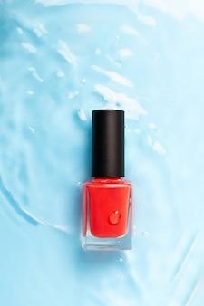 Бутылка красного цвета покрасила маникюр на открытом море, конец вверх. вид сверху.