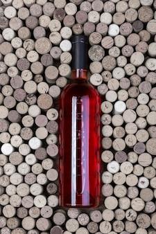 木製のテーブルに赤ワインとコルクのボトル