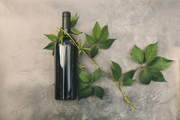 빈티지 어두운 돌 테이블 배경에 레드 와인과 녹색 포도 나무의 병. 텍스트의 상위 뷰 복사 공간입니다. 와인 가게 와인 바 와이너리 또는 와인 시음 개념.