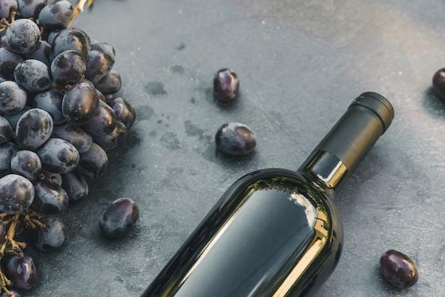ヴィンテージの暗い石のテーブルの背景に赤ワインと熟したブドウのボトル。テキスト用の上面コピースペース。ワインショップワインバーワイナリーまたはワインテイスティングのコンセプト。
