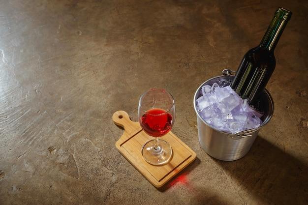 氷のバケツに入った赤ワインのボトルと赤ワインのグラス