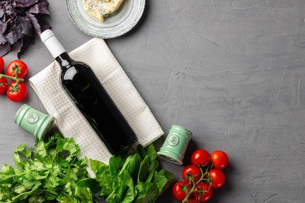 野菜の上面図と灰色の表面に赤ワインのボトル