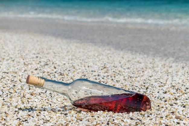 Бутылка красного вина на пляже в солнечный летний день