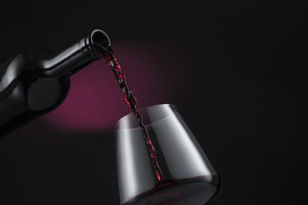 Бутылка красного вина наливают в бокал