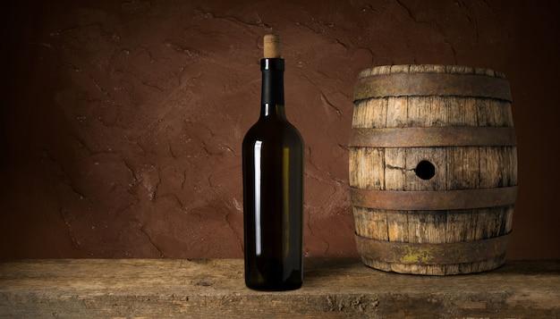코르크와 레드 와인 한 병입니다. 검은 나무 배경에.