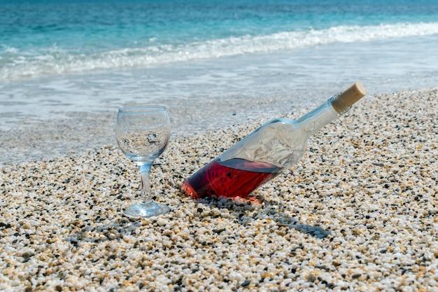 Бутылка красного вина с бокалом для вина на пляже в летний солнечный день