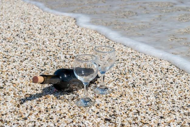 Бутылка красного вина с фужерами на пляже в солнечный летний день