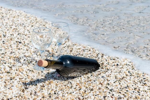 Бутылка красного вина с фужерами на пляже летом