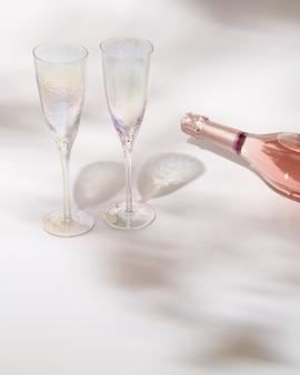 장미 와인 한 병과 햇빛과 자연 그림자가있는 두 개의 크리스탈 잔