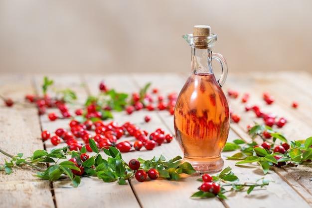 Бутылка масла шиповника на деревянной палитре с ягодами вокруг