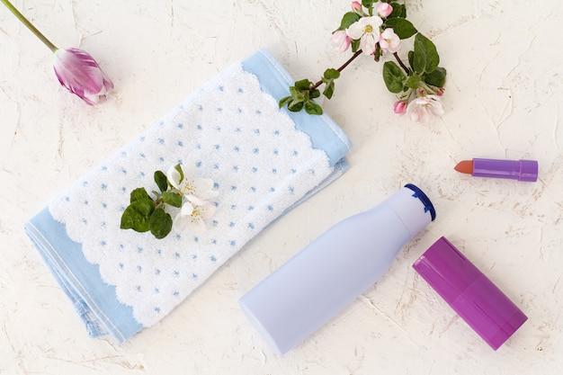 샴푸 한 병, 수건, 탈취제, 립스틱, 구조화된 배경에 사과 나무 꽃. 목욕 절차를 위한 여성용 액세서리. 평면도.