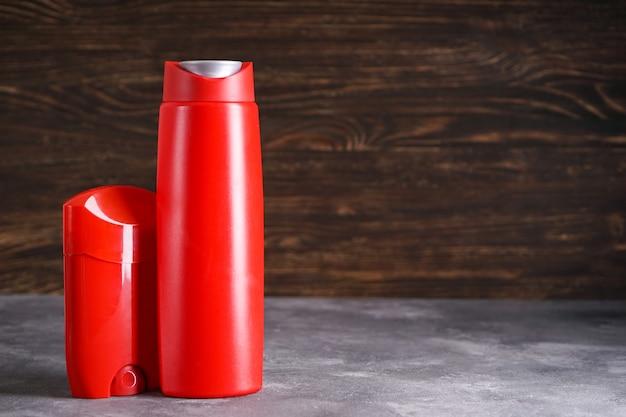 Бутылка шампуня и дезодоранта на деревянном фоне. место для текста.