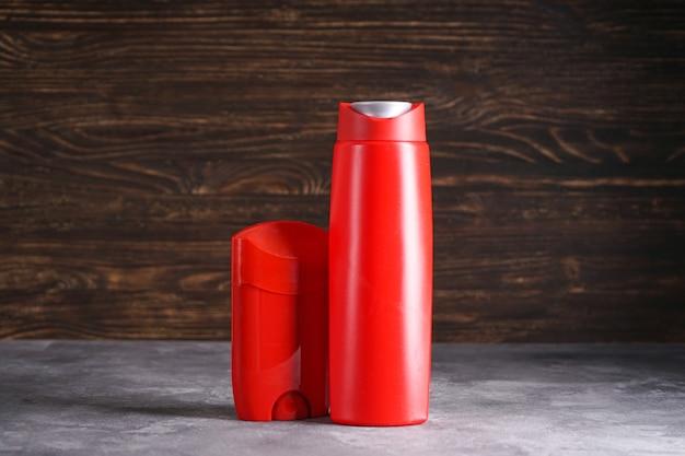 Бутылка шампуня и дезодоранта на деревянных фоне.