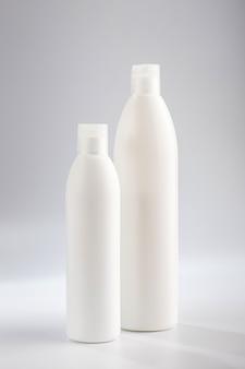 Бутылка шампуня и кондиционера для волос на серой стене. моющие средства для ухода за волосами.