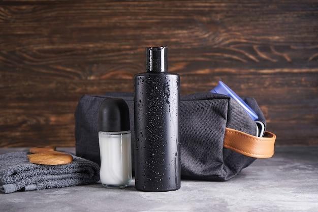 Бутылка шампуня, дезодоранта и полотенца на деревянном фоне. место для текста.