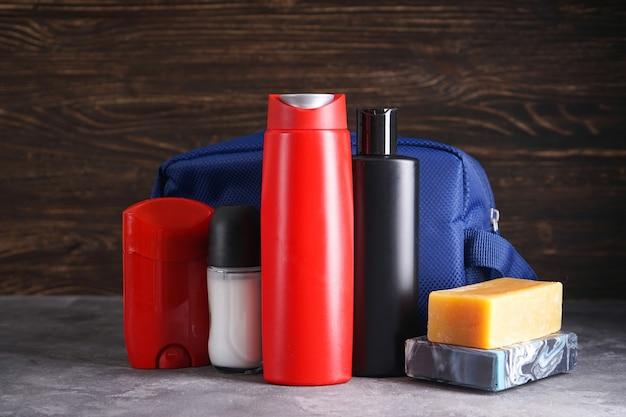Бутылка шампуня, дезодоранта, мыла и ухода за телом на деревянном и сером фоне.