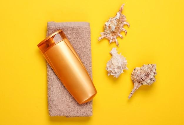 Бутылка шампуня с минералами и ракушками, полотенце на желтом. уход за волосами