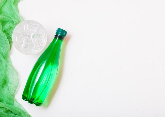 Бутылка газированной минеральной воды и стакан льда