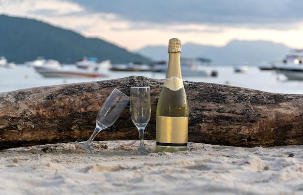 ビーチでシャンパングラスとスパークリングワインのボトル