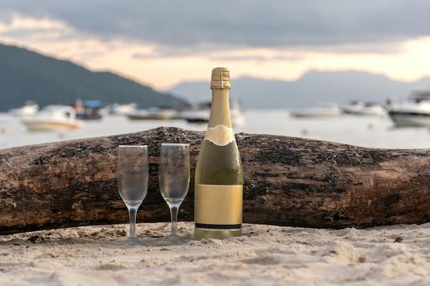 ビーチでグラスとスパークリングワインのボトル