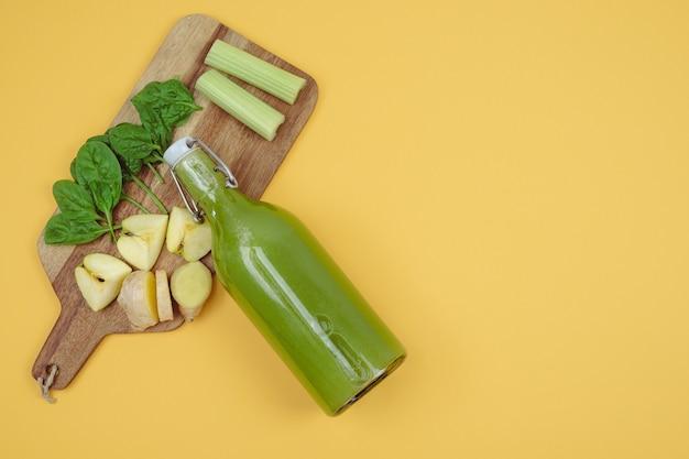ほうれん草ジュースと野菜と果物のクッキングボードのボトル。コピースペース。