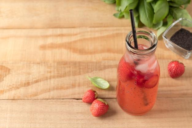 Бутылка клубничного напитка с семенами базилика на деревянном столе необычный освежающий летний напиток