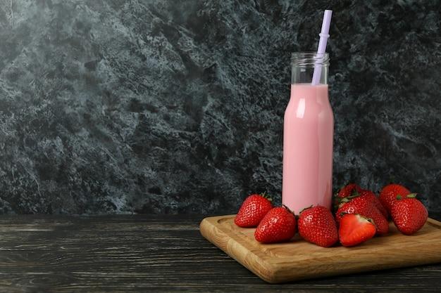 딸기 밀크 쉐이크와 나무 테이블에 재료의 병
