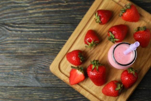 나무 테이블에 딸기 밀크셰이크와 재료 한 병