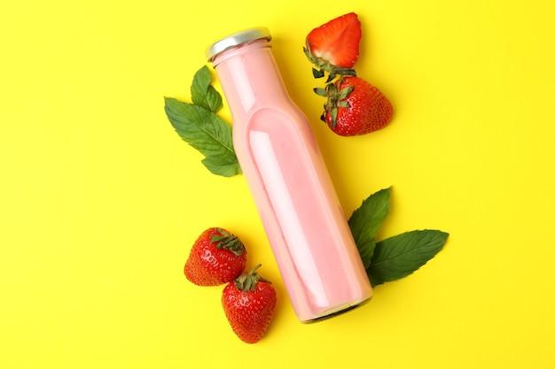 딸기 밀크 쉐이크와 노란색 배경에 재료의 병