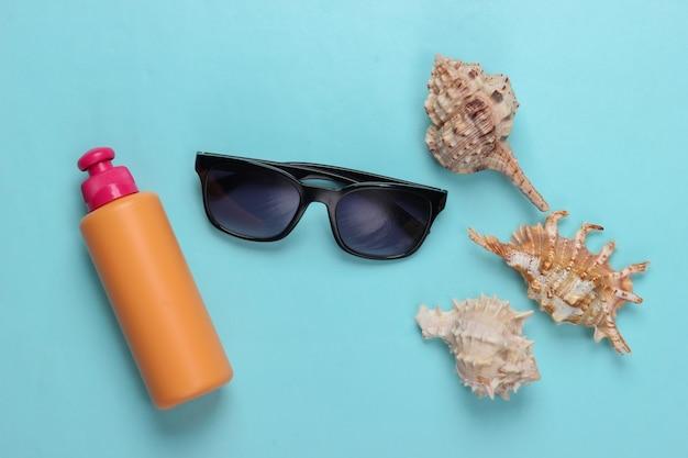サングラス、青の貝殻と日焼け止めのボトル