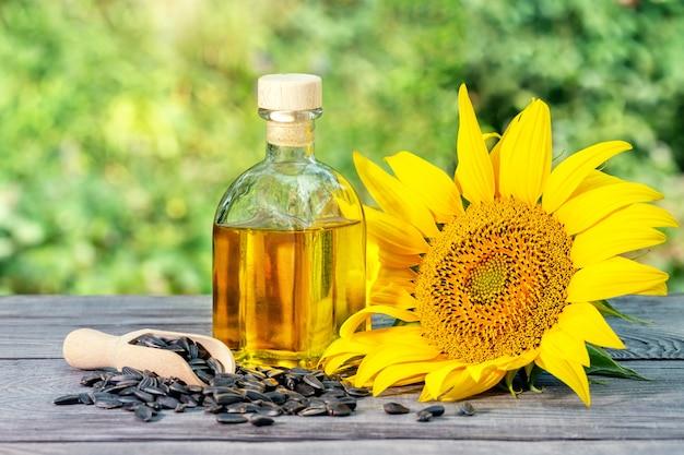 Бутылка подсолнечного масла и подсолнечника цветы с семенами на деревянный стол