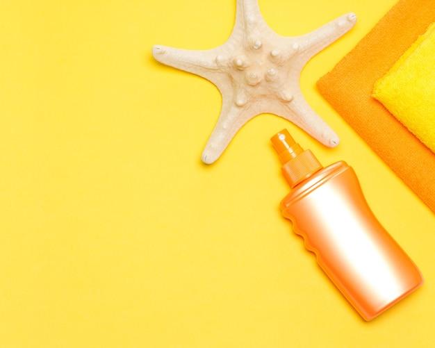 Бутылка солнцезащитного спрея с морскими звездами и полотенцами. лосьон для загара. копировать пространство
